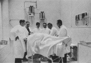 Fotograbado, igualmente publicado en Ecos Españoles de Dermatología y Sifiliografía en 1927, en el que aparece Sainz de Aja rodeado de varios colaboradores realizando una intervención quirúrgica.