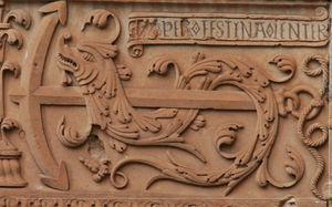 Patio de la Universidad de Salamanca. Enigmas (s. XVI). Sexto enigma: Festina lente (apresúrate despacio). El ancla sobre el delfín es idea de contraposición, de lo lento (ancla) y lo rápido (delfín).