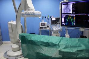 Sala de angiografía preparada, con cobertura plástica del equipo, antes de la llegada del paciente.