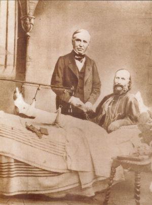 Retrato de Auguste Nélaton y Giuseppe Garibaldi estrechando manos (nótese que el cirujano francés está comprobando con su mano izquierda el pulso arterial de su paciente). Garibaldi, herido y tendido en la cama, acaba de recibir la noticia de que su pierna no será amputada (foto por DeAgostini / Getty Images).