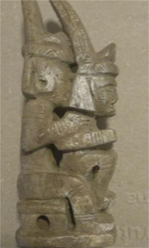 Escultura en hueso de un par de amantes heterosexuales en la típica posición de symplegma, sentada en los muslos del hombre y de espaldas a él con penetración anal de la mujer. Cultura Tairona. La escultura tiene 15.5cm de alto, 4.7cm de largo y 2.9cm de ancho.