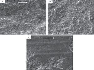 Análisis morfológico por MEB de la superficie de la huella de desgaste de los recubrimientos de (a) YSZ, (b) CSZ y (c) ATZ, después del ensayo bola-disco. La flecha en cada micrografía indica la dirección del paso de la bola, y CA es la capa adhesiva.