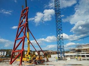 Hoisting the first truss panel: note the provisional props used to stabilise the structure during erection.