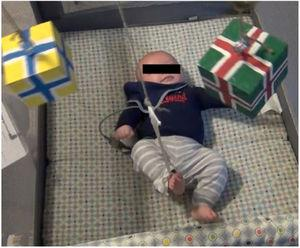 The mobile paradigm set-up. Infant's right leg is tethered to the right stand, and thus the kicking movement causes the mobile to move when the mobile is attached to the right stand during the acquisition period. The mobile is composed of five wooden blocks and five bells to provide both visual and auditory feedback.