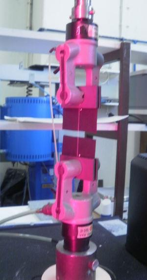 Specimen clamped with pneumatic grips and illuminated by the video extensometer, during a tensile test, where the yarn deformation is already meaningful.